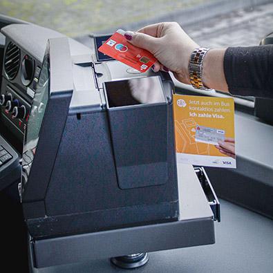 Person zahlt in Bus mit Karte an cVEND plug Terminal